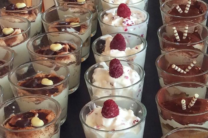 Eine Dessertauswahl: Tiramisu für Kinder ohne Alkohol - mit Apfelmuss. Himmelstraum mit Himbeeren, verziert mit Himbeere. Tiramisu mit Kakao und Schokoröllchen