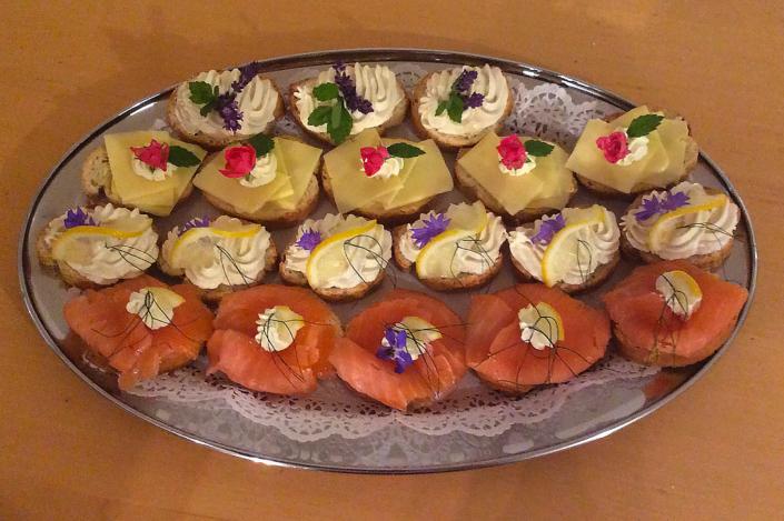 Canapes mit Frischkäsemousse mit Lavendel und Minze verziert. Canapes mit Heumilch Sennerkäse, Kräutermousse, essbarer Rose und Minze verziert. Canapes mit geräuchertem Forellenfilet Mousse, essbarer Kornblume, Zitrone und Dill. Canapes mit geräuchertem Lachs, Meerrettich Mouse, Zitrone, essbarem Borretsch und Dill