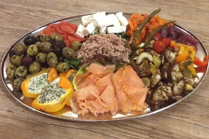 Antipasti mit Oliven, Cervelat, Feta, Variationen von gegrilltem Gemüse, geräucherter Lachs, gefüllte Paprika und Thunfisch, gewürzt mit Knoblauch und Chili